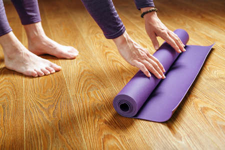 A woman lays out a lilac yoga mat on the wooden floor. Women practicing yoga. A healthy lifestyle in isolation.