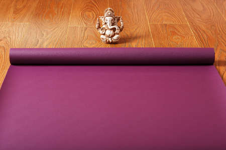 A lilac-colored yoga mat is spread out on the wooden floor with a Ganapati figurine. Top view Standard-Bild