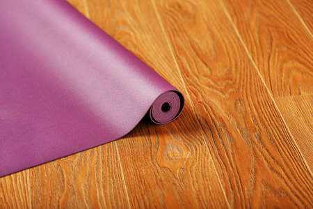 An unfolded lilac-colored yoga mat is unfolded on the wooden floor. Top view