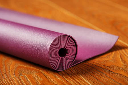 A lilac-colored yoga mat is spread out in a roll on the wooden floor. Close-up