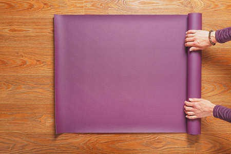 A woman's hands lay out a lilac yoga or fitness mat before a workout practice at home on a wooden floor. Healthy lifestyle, asana and meditation practices