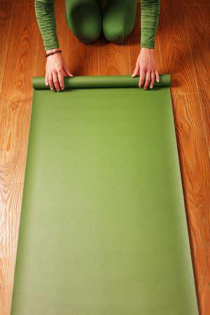 A woman rolls out a green mat before a yoga class.