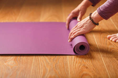 A girl lays out a lilac yoga mat before a workout practice at home on a wooden floor. Healthy lifestyle, asana and meditation practices Standard-Bild