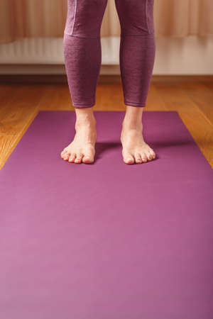 Legs and hands of a woman on a yoga mat practicing asanas. A healthy lifestyle at home in isolation.