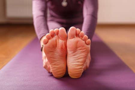 Girl practicing yoga leaning forward sitting, feet forward-paschimottanasana pose, training on a lilac mat. Standard-Bild