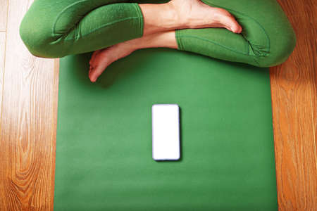 A woman watches yoga classes on her smartphone while sitting on a green exercise mat. The concept of training in the living room of the house. Technology and sports
