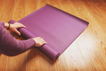A man lays out a lilac yoga mat on the wooden floor of a house. Standard-Bild