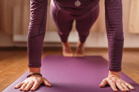The girl does yoga in the asana stand on a lilac mat. Healthy lifestyle, asana and meditation practices Standard-Bild