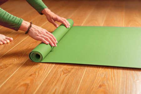 A woman collects a green mat after a yoga class. Standard-Bild