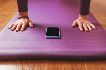 A girl does yoga with a smartphone online via the Internet on a lilac rug in the living room.