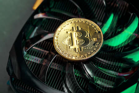 Gold bitcoin on the video card cooler with green neon lighting in the Cyberpunk style. The concept of mining and mining of cryptocurrencies, the device of a cryptocurrency farm.