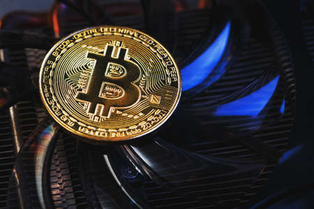 Gold Bitcoin on the video card cooler on a dark background top view. The concept of mining and mining of cryptocurrency, the device of a cryptocurrency farm. Macro, Top View, Selective Focus