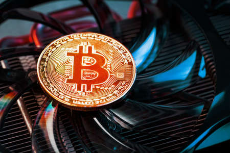 Gold bitcoin coins lie on the cooler of a powerful video card with cyanide neon illumination. Standard-Bild