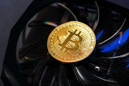 Bitcoin on a graphic card with a blue neon light on a dark background. Cryptocurrency Mining Concept. Macro, Top View, Selective Focus