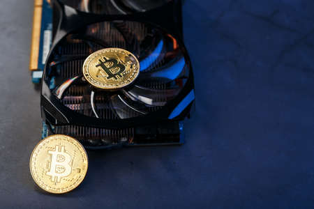 Bitcoin coin on a powerful graphics card for mining and earning cryptocurrency concept on a dark background. Technologies of the future currency. Top View, Selective Focus Standard-Bild
