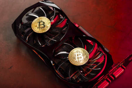 On the fans of a powerful video card, the coins of the Bitcoin cryptocurrency with a red backlight are displayed. The concept of mining and mining of cryptocurrency a cryptocurrency farm.