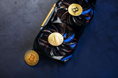 Gold Bitcoin on the video card cooler on a dark background top view. The concept of mining and mining of cryptocurrency, the device of a cryptocurrency farm.