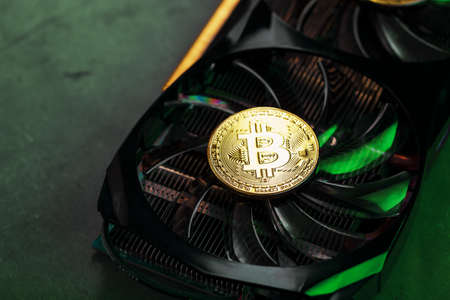 On the powerful fans of the video card there are coins of the Bitcoin cryptocurrency with a green backlight. Macro Standard-Bild
