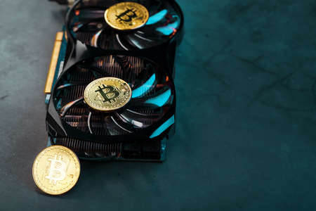 Gold bitcoins on a video card with a blue backlight in the style of cyberpunk. Cryptocurrency. Bitcoin Mining Concept