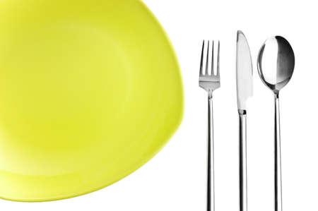 Зеленая тарелка, вилка, нож и ложка на белом фоне
