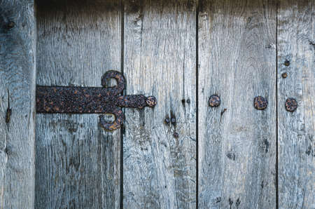 part of old wooden gate with rusted iron hinge Stock Photo