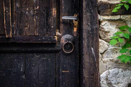 Часть старой коричневой деревянной двери с ржавым железным кольцом