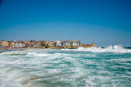 Вид на море с волнами и старым городом на фоне