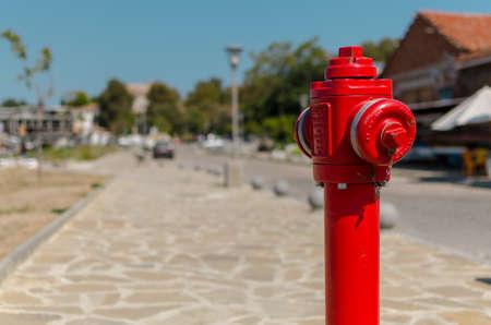красный пожарный гидрант на улице на фоне размытого Фото со стока