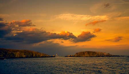 Панорамный вечер зрения двух островов на закате с драматические облака в Созополь, Болгария Фото со стока