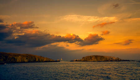 panoramic evening view of two islands at sunset with dramatic clouds in sozopol, bulgaria