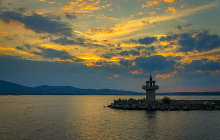 panoramic evening view of lighthouse at sunset with dramatic clouds in sozopol, bulgaria