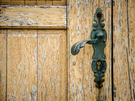 часть старой деревянной двери с дверной ручкой
