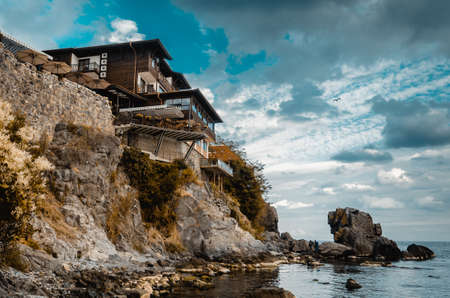 lonely old house on a rock cliff on seashore Stock Photo