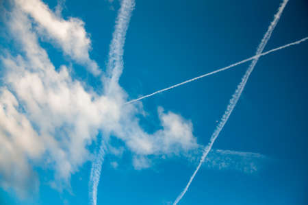 contrails of jet planes and clouds in blue sky Stock Photo