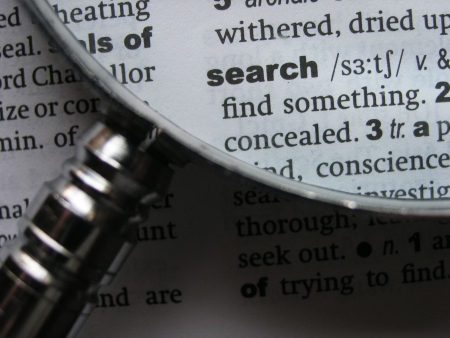 Magnifying glass on dictionary page with the word search. photo