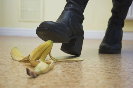 cause: Banana skin lies ready to cause a painful slip-up. Slapstick concept illustrating danger and pitfalls. Stock Photo