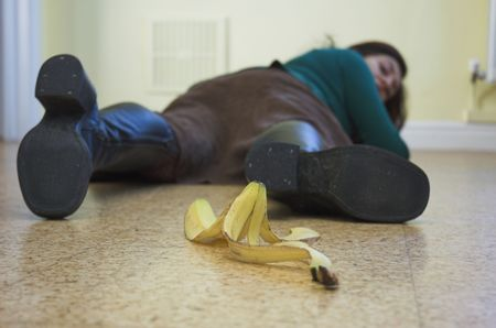 Banana causes a painful slip-up. Slapstick concept illustrating danger and pitfalls. Stock Photo - 655253