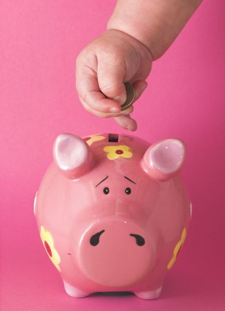 prudent: Baby deposits coin in cute pink piggy bank on a pink background.