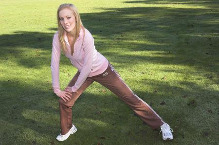 warm up: Una giovane donna si estende fino a caldo prima di esercitare in un parco.  Archivio Fotografico