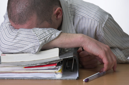 cramming: Male student slumped over his work after cramming for exams.