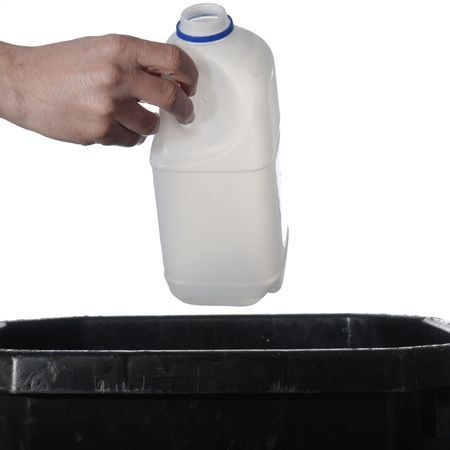Man dropping plastic milk bottle into a recycling bin. Isolated on white. Stock Photo - 3312721