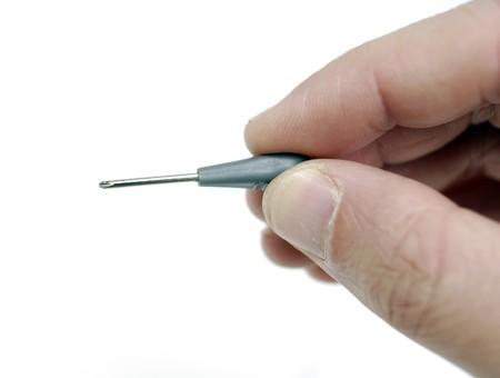 tweak: Hand holding mini screwdriver.
