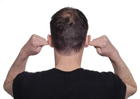 annoyance: Young man with his fingers in his ears to block out noise.