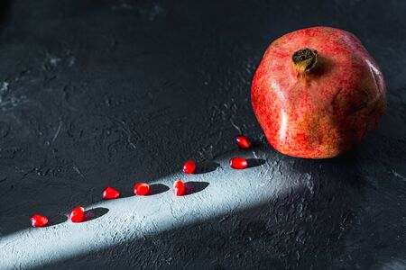 ripe red pomegranate on and grain on a gray background Stok Fotoğraf - 133878367
