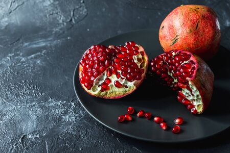 ripe red pomegranate on and grain on a gray background