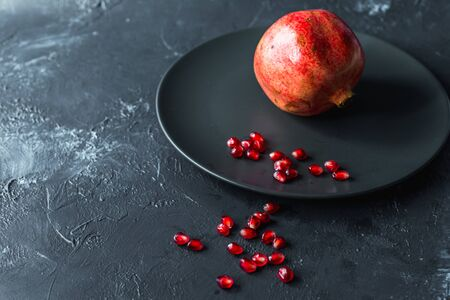 ripe red pomegranate on and grain on a gray background Stok Fotoğraf - 133878380