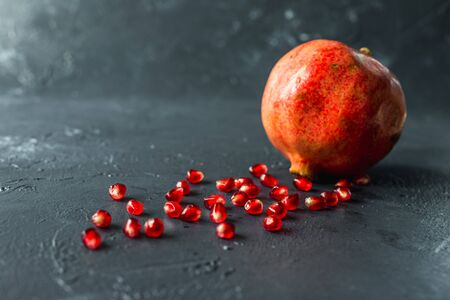 ripe red pomegranate on and grain on a gray background Stok Fotoğraf - 133878383