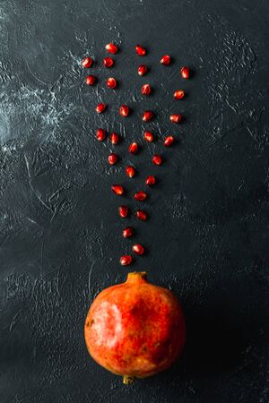 ripe red pomegranate on and grain on a gray background Stok Fotoğraf - 133878384