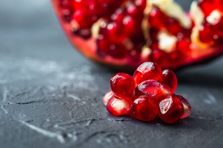 ripe red pomegranate on and grain on a gray background Stok Fotoğraf - 133878452