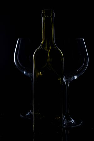 glass of red and pink wine on a black background. Wine list menu. Close up of the power of glasses and bottles in low key